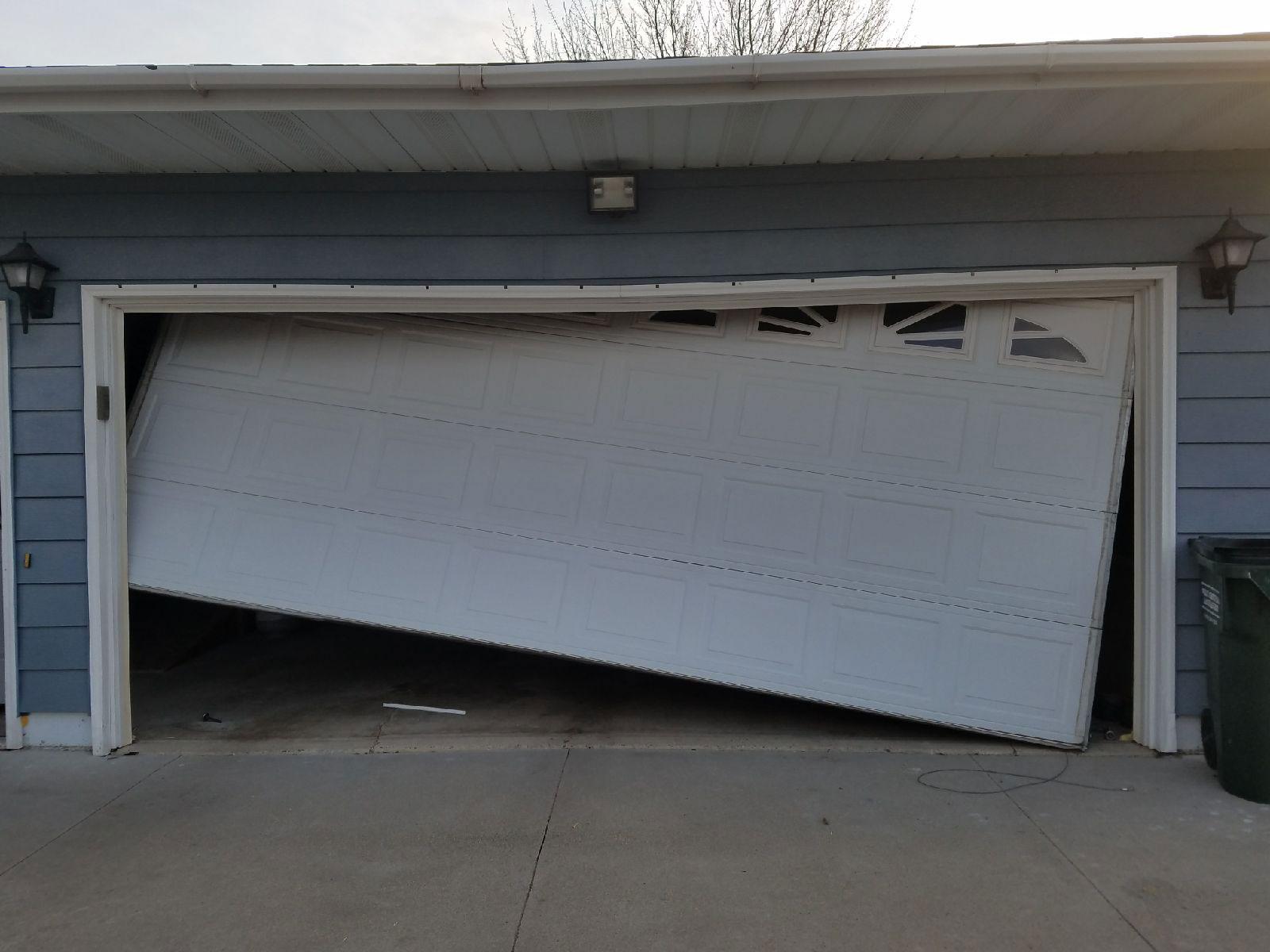 Crashed garage door with a bent track